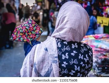 Shiraz, Iran - October 23, 2016: Iranian woman with small baby on the Vakil Bazaar in Shiraz