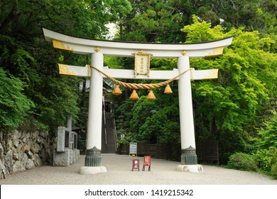 """Shirine big gate """"Torii"""". Japanese text on gate is """"Hotosan Jinja Shirine"""". Red right sign  """"No dogs allowed inside"""". Left sign """"Car Stop"""". Rear sign """"Hotosan account on Facebook etc."""". Japan."""
