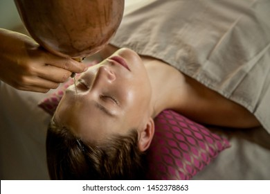 Shirodhara, an Ayurvedic healing technique. Oil dripping on the female forehead. Portrait of a young woman at an ayurvedic massage session with aromatic oil dripping on her forehead and hair.