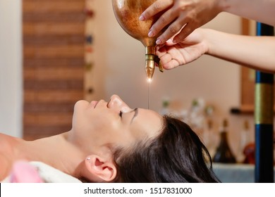 Shirodhara, an Ayurvedic healing technique. Oil dripping on the female forehead. Portrait of a young woman at an ayurvedic massage session with aromatic oil dripping on her forehead and hair