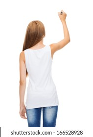 shirt design and advertisement concept - teenage girl in blank white shirt from the back drawing or writing something in the air