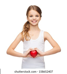 shirt design, health, charity, love concept - smiling teenage girl in blank white shirt with small red heart