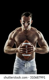 Shirtless American football player with ball on black background