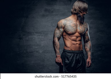 Shirtless athletic bearded hipster male with tattooed muscular body on grey vignette background.