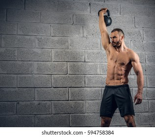Shirtless athletic bearded male doing workouts with dumbbells over grey wall background.