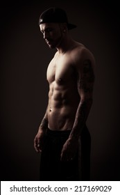 shirtless athletic muscular male model wearing cap posing side view color toned
