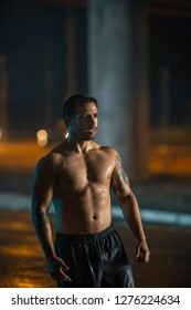 Shirtless Athletic Muscular Young Man is Finishing His Sport Trainig on a Rainy Night. He is in an Urban Environment Under a bridge with Cars in the Background.