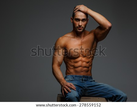 208b89f7 Shirtless attractive muscular guy in blue jeans sitting on podium on grey  background