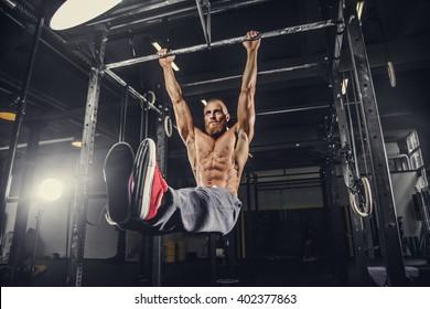 Shirtless bearded man doing stomach exercises on a horizontal bar.