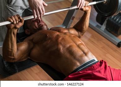 shirtless bodybuilder doing bench press for chest