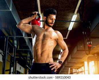 Shirtless bodybuilder. handsome young man training hard and lifting dumbbells, training arms at gym