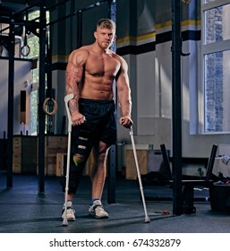 Shirtless bodybuilder on crutches near cross fit stand in a gym.