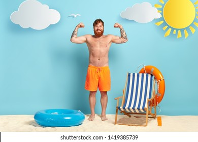 Shirtless cheerful ginger man raises arms, shows muscles, has tattoo, wears orange shorts, poses on sand, inflated swimring, lifebuoy, beach chair around. Happy guy feels proud of having abs