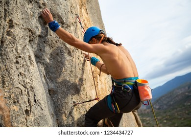 Shirtless climber man climbing mountain wall on amazing sunny day