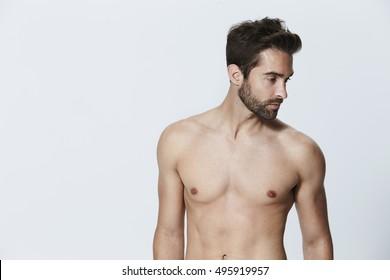 Shirtless dude looking away in studio