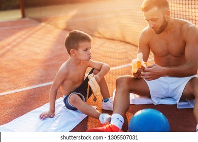 Shirtless father and son sitting on the court, eating bananas and resting after exercising. Summertime at morning.
