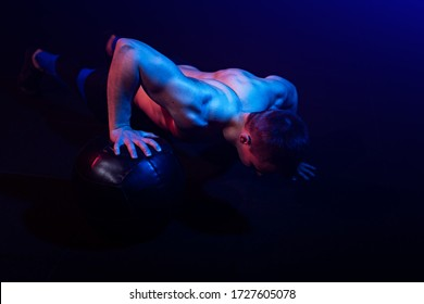 Shirtless fit young muscular is working out with a medicine ball in gym in dark fitness studio colored with complementary color gels
