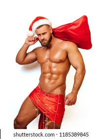 Shirtless fitness model with christmas hat and bag for gifts