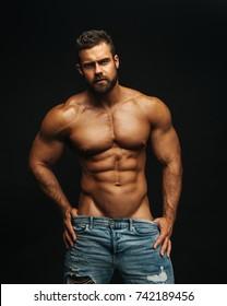 Shirtless fitness model Konstantin Kamynin on black background