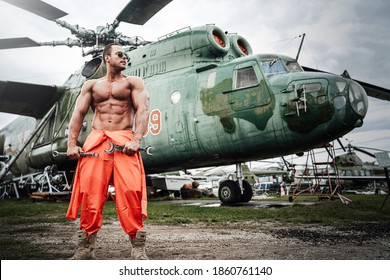 Shirtless guy in orange clothing with muscular build and sunglasses poses in background of helicopter holding wrenches.