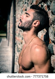 Shirtless handsome athletic young man outdoor standing against old brick wall looking down to a side