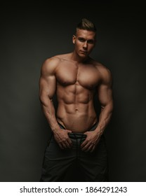 Shirtless handsome young guy in pants standing in studio at grey background