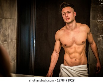 Shirtless handsome young man looking at himself in bathroom mirror in the morning