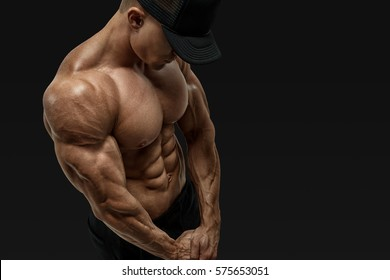 Shirtless male bodybuilder with muscular build strong abs showing. Perfect fit, six pack, abs, shoulders, deltoids, biceps. Bodybuilder with muscular physique looking down. Vector clipping mask path