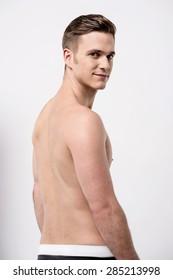 Shirtless male model looking over shoulder