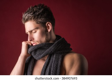 Shirtless male model wearing a scarf - Young handsome man against a dark red background