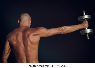 Shirtless man athletic body lifts dumbbell rear view on dark background.