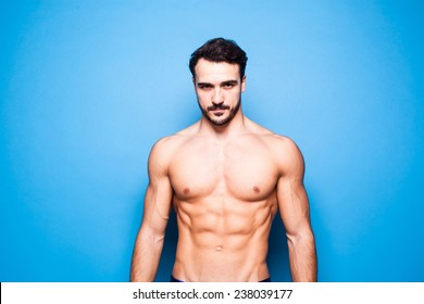 shirtless man with beard on blue background