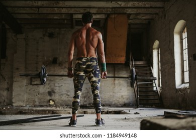 Shirtless man deadlift and holding barbell in top position in a deserted building