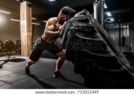 Are you working out hard enough--Shirtless man flipping heavy tire at gym
