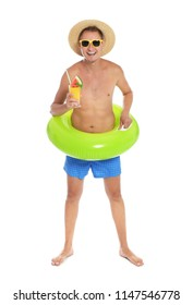 Shirtless man with inflatable ring and glass of cocktail on white background