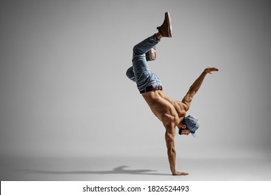 Shirtless man in jeans doing a handstand isolated on gray background