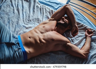 Shirtless man lying in the bad and smiling. Natural morning light