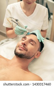 Shirtless man lying with closed eyes and careful beautician nourishing the skin on his forehead