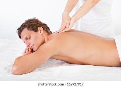 Shirtless Man Lying On Front Getting Spa Treatment