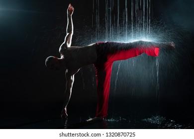 Shirtless man practicing qigong under the rain