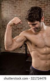 Shirtless man showing his biceps at the gym