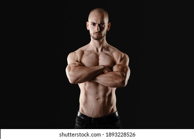 shirtless man standing with crossed arms looking at camera with narrowed eyes and serious face expression beeing proud of sprotive success