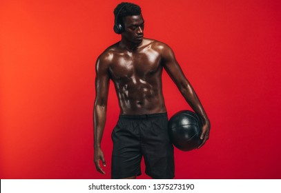 Shirtless man standing with medicine ball against red background. African american guy with muscular body holding a fitness ball and looking away.