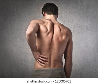 Shirtless man touching his back for the pain
