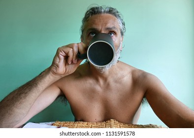 shirtless mature man drinking a cup of coffee