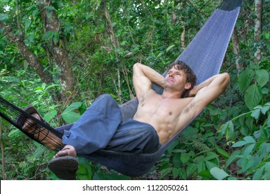 Shirtless muscular adventure man relaxing in black hammock hung in jungle wilderness of Chiapas, Mexico