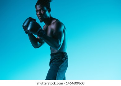 shirtless, muscular african american sportsman boxing on blue background