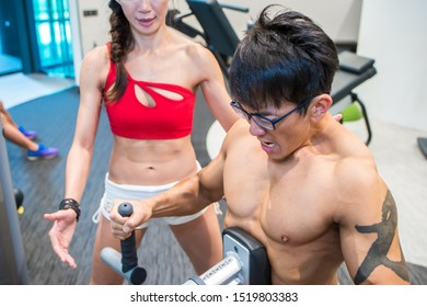 Shirtless muscular body asian Chinese man exercising training abs doing workout in indoor gym with female fitness personal instructor