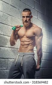 Shirtless muscular guy posing over grey background.