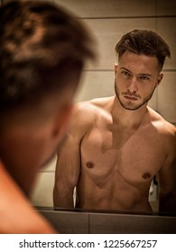 Shirtless muscular handsome young man looking at himself in bathroom mirror in the morning